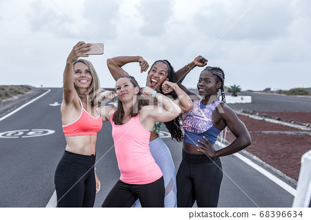 Multiracial sportswomen showing biceps and taking 68396634