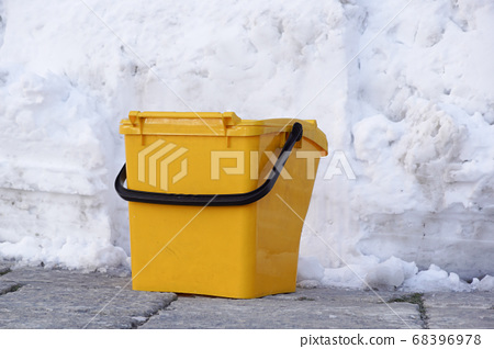 Yellow trash on the walkway. Yellow trash and trees. Yellow trash beside the wall 68396978