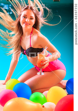 Happy woman with balloons and cocktail at poolside 68397350