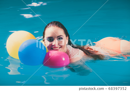 Happy woman in water having fun with balloons 68397352
