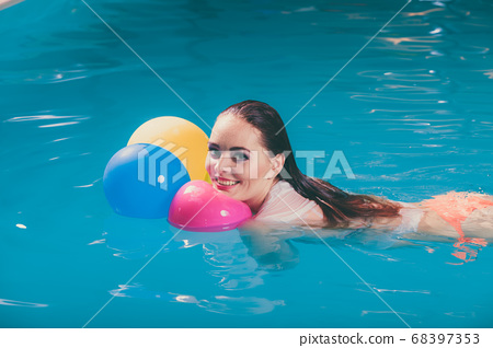 Happy woman in water having fun with balloons 68397353