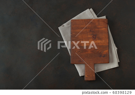 Wood cutting board over towel on stone kitchen 68398129