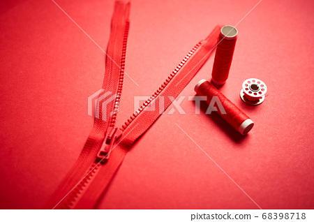 threads and zipper on a red minimalistic background 68398718