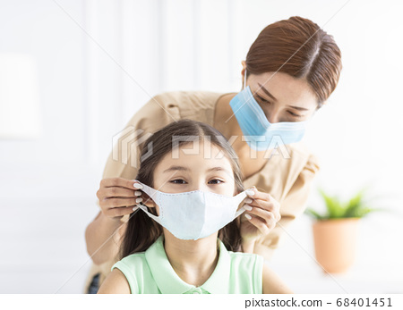 mother help her daughter wearing healthy face mask 68401451
