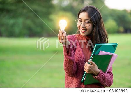 Creative young woman hold shinning light bulb. 68405943