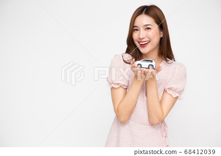 Young Asian woman holding car model. 68412039