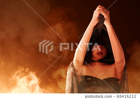 Asian witch woman with black cloak holding a knife 68416212