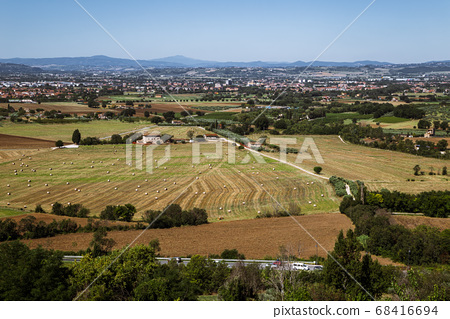 Panoramic view of farmland green field and rural village in Assisi, Umbria, Italy 68416694