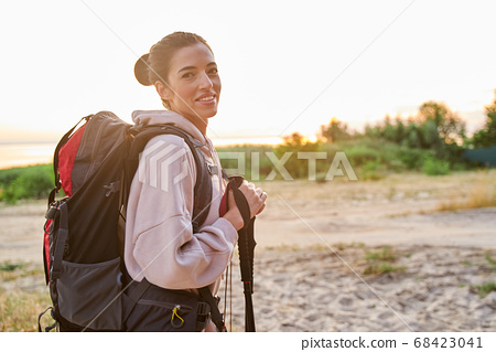Cheerful young woman with backpack hiking alone 68423041