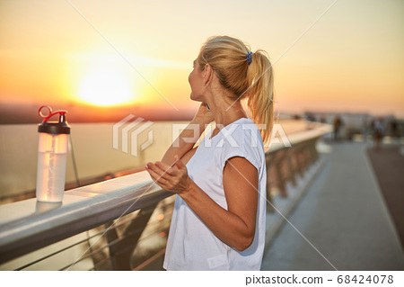 Blonde woman talking on her smartphone outside 68424078