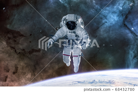 Astronaut in orbit of the Earth. Solar system, nebulae. Science fiction 68432780