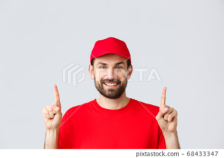 Online shopping, delivery during quarantine and takeaway concept. Cheerful bearded smiling courier in red uniform cap and t-shirt, invite take look at promo, pointing fingers up, grey background 68433347