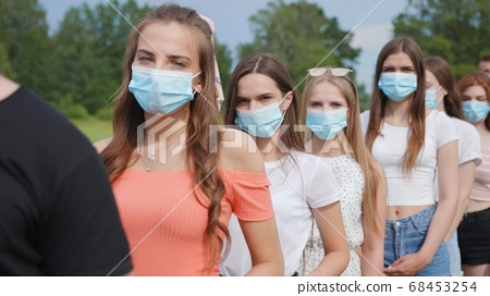 Pandemic concept. A group of students stand in a row in masks. 68453254