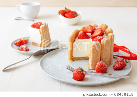 Charlotte, French strawberry dessert, tied up with a scarlet ribbon, cup of coffee, white background 68459119