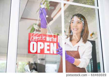 Asian woman wearing face shield cleaning glass prepared for reopen her cafe 68460089
