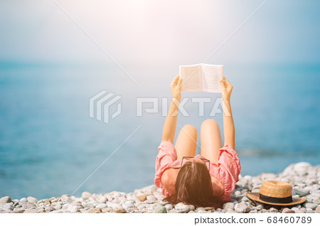 Young woman reading book during tropical white beach 68460789