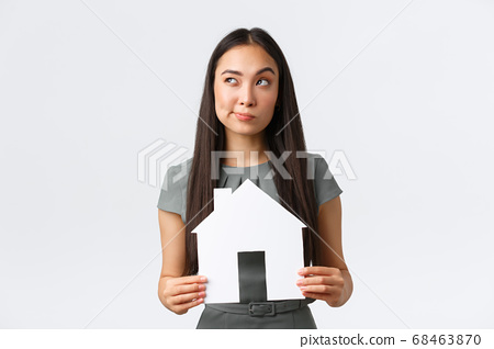Insurance, loan, real estate and family concept. Thoughtful and doubtful asian woman thinking about buying new apartment, holding paper house and looking away, pondering, making decision 68463870