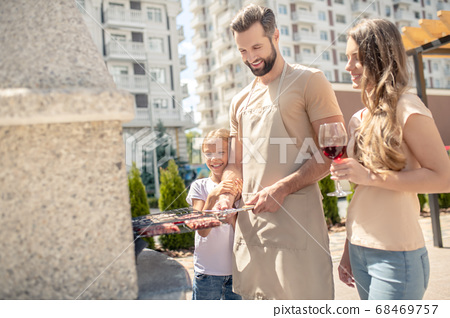 Beautiful family having barbeque and looking happy 68469757