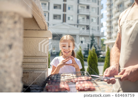 Cute kid watching her dad grilling meat 68469759