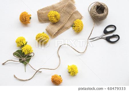 marigold yellow flowers on sack ,scissors ,rope arrangement flat lay postcard style 68479333