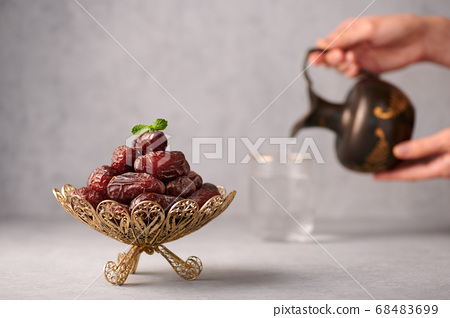 Date Fruits or Kurma in vintage arabic dish and jug of water at grey concrete background 68483699