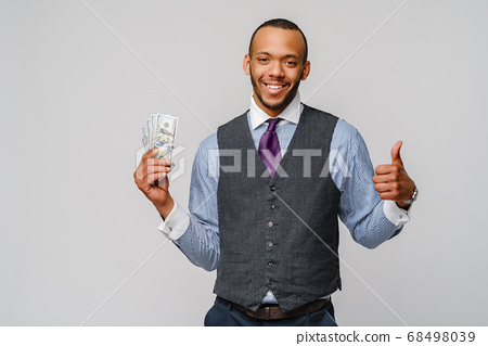 Portrait of excited young african american man holding cash money and showing thumb up over light grey background 68498039