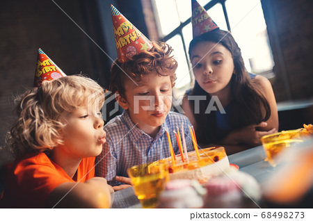 Three kids sitting at the table and blowing out the canldes 68498273