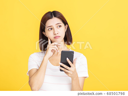 young asian woman holding mobile phone and looking 68501798