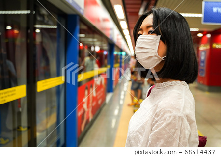 young adult Asian woman wearing a face mask on subway playform waiting for train 68514437