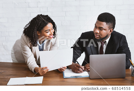 Sexual harassment in office. Black businesswoman flirting with her displeased male secretary at workplace 68514558