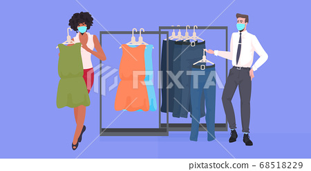 salesman in mask showing clothes to female customer in fashion boutique coronavirus pandemic quarantine 68518229