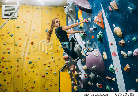 Young woman climbing a tall, indoor, man-made rock climbing wall 68520085