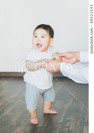 Cheerful baby grabs and stands in the room 68521543