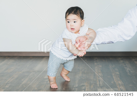 Cheerful baby grabs and stands in the room 68521545