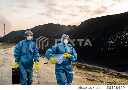 Two female ecologists in coveralls, respirators, eyeglasses and rubber gloves 68528449