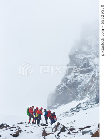 Group of mountaineers standing on snowy hillside. 68529550