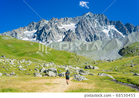 Woman with backpack hiking towards mountain top, 68530455