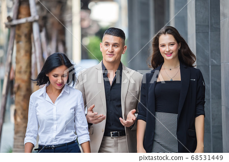 Happy business people partners  teamwork wearing suits walking on city street. 68531449