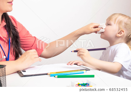 Doctor pediatrician wipes the nose from snot to a child a little girl 3 years old. The concept of treating a runny nose in children and nasal congestion. Bacterial infection, copy space 68532455