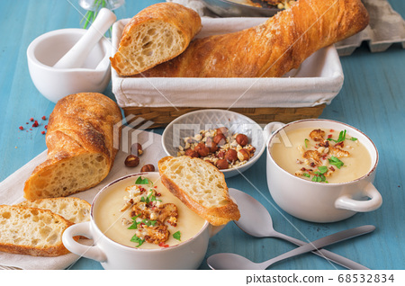 Homemade creamy caulifower soup with crushed hazelnuts, red pepper, parsley and Swiss twisted bread. 68532834
