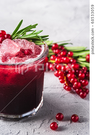 Fresh ice cold fruit cocktail in glass, refreshing summer red currant berry drink with rosemary leaf 68533059