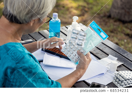 Stressed senior woman many daily expense with face mask,hand sanitizer,medicine because of epidemic,outbreak of Covid-19,elderly worry about wasting money,financial problem,family expenditure  68534231