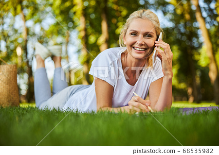 Cheerful woman talking on mobile phone in park 68535982