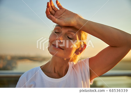 Charming woman placing hand on her forehead 68536339