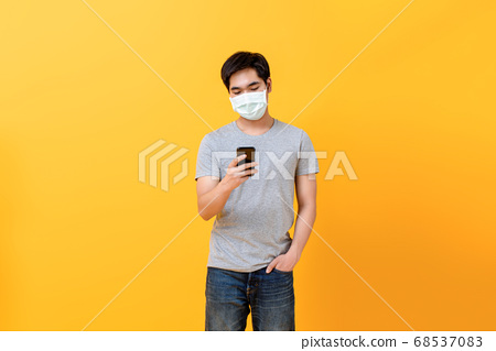 Young Asian man wearing medical face mask with mobile phone 68537083