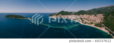 Panorama from the drone. The coast of Budva in Montenegro and the island of St. Nicholas. The isthmus between the island and the city. Green spring mountains. The city on the adriatic coast. 68537612