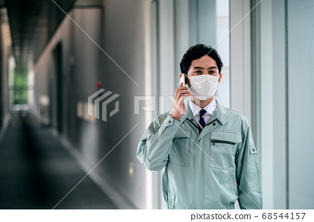 Engineer wearing work clothes in a mask calling in the office corridor 68544157