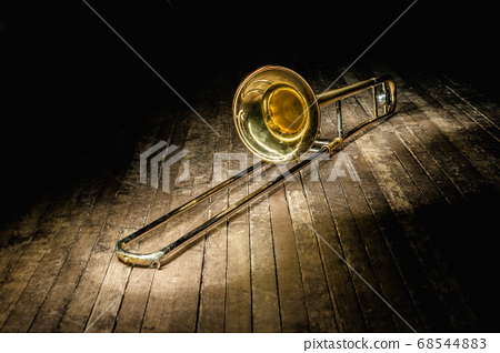 golden brass instrument trombone lies on a dark 68544883