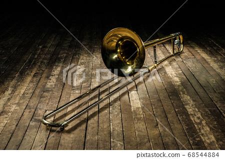 golden brass instrument trombone lies on a brown 68544884