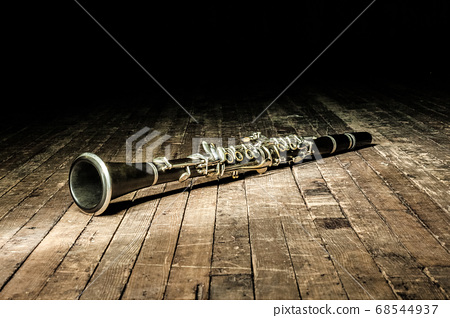 black woodwind clarinet lies on a brown wooden 68544937